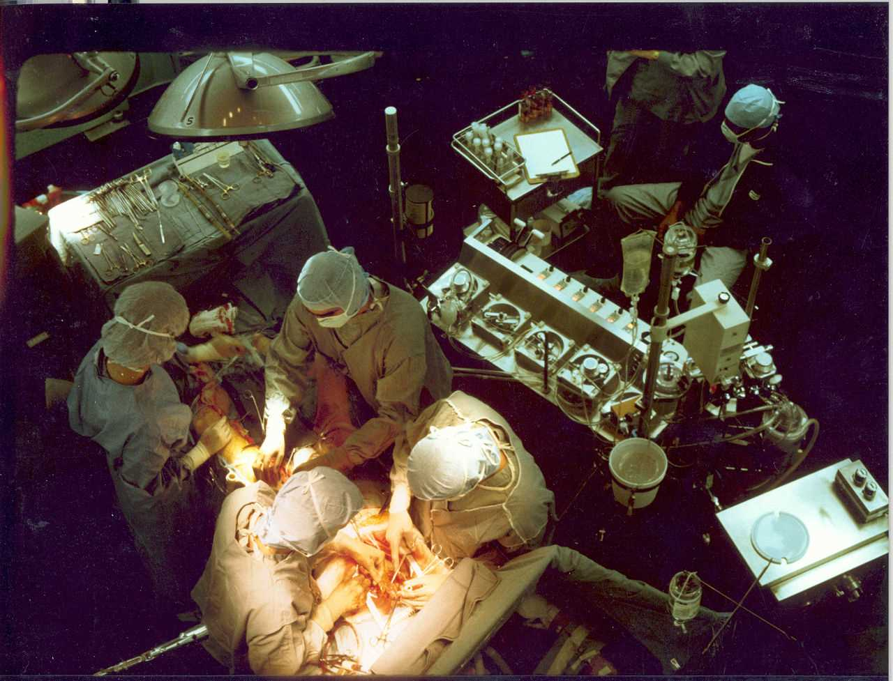 Early in a coronary artery bypass operation, during vein harvesting from the legs (left of image) and the establishment of cardiopulmonary bypass by placement of an aortic cannula (bottom of image). The perfusionist and heart-lung machine are on the upper right. The patient's head (not seen) is at the bottom.